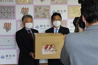 (画像:マスクの箱を間に荒木恵司市長と森社長)